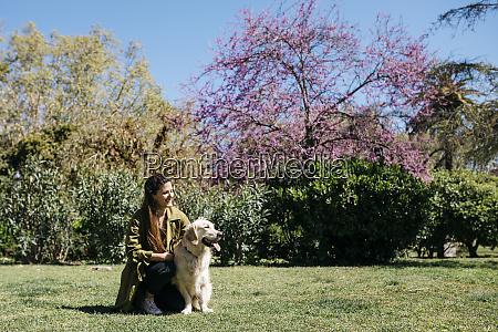 happy woman stroking her labrador retriever