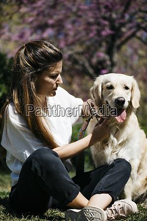 woman and labrador retriever sitting