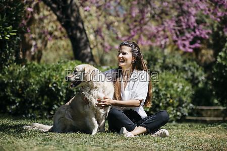 happy woman sitting on meadow in