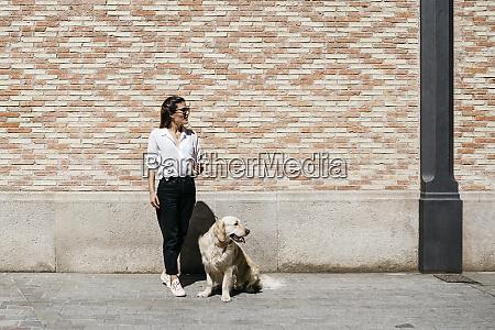 woman and her labrador retriever waiting