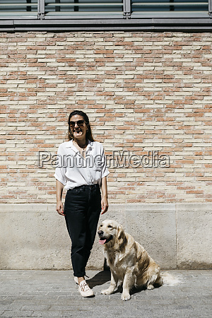 laughing woman standing besides her labrador