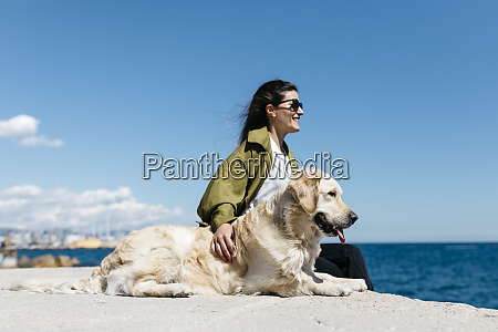 happy woman sitting besides her labrador