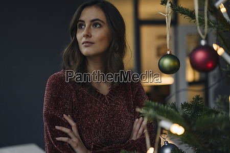 young woman at decorated christmas tree