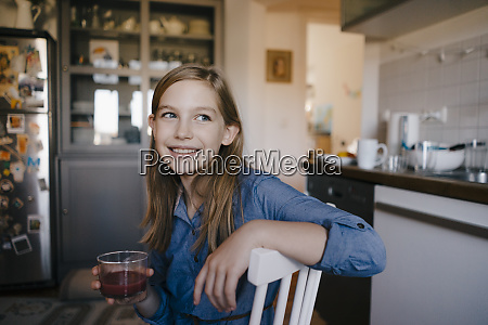happy girl sitting at kitchen table
