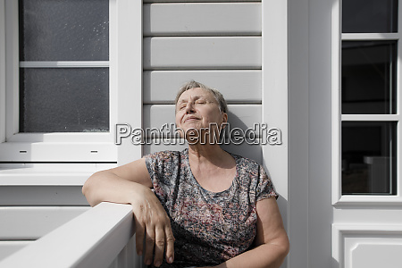 relaxed senior woman sitting on porch