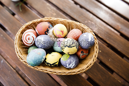 easter eggs in basket on wooden