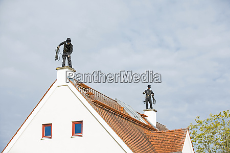 two chimney sweeps working on house