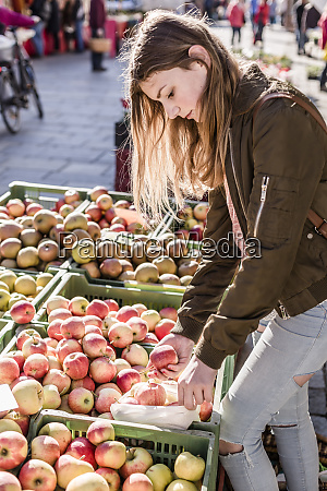 girl with cloth bag choosing apples