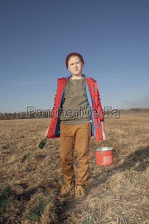 serious boy with paint bucket and