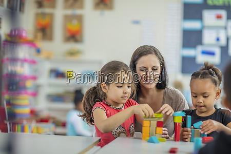 pre school teacher playing with girls