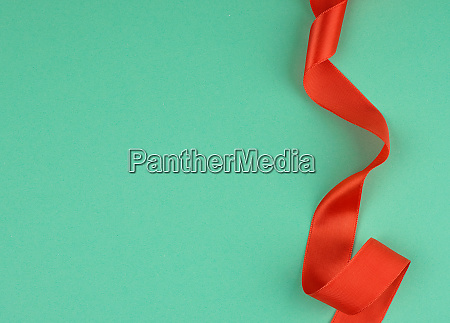 twisted red silk ribbon green background