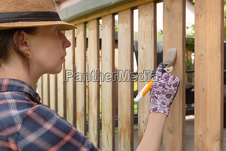 woman with a paintbrush painting wooden