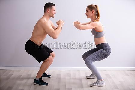fitness couple in sportswear doing squat
