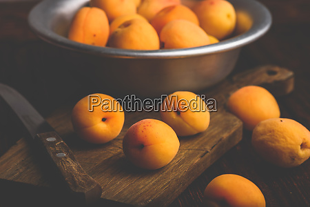 mellow apricots with knife over cutting
