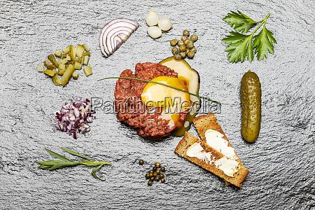 raw steak tartare on black slate