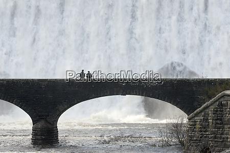 visitors walk across a bridge as