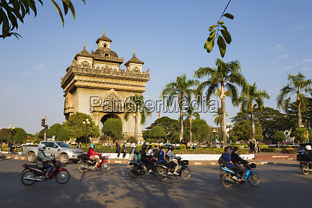 mopeds riding past the patuxai victory