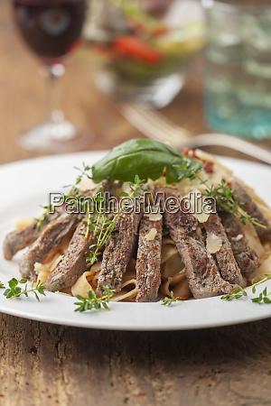 steak slices on italian pasta
