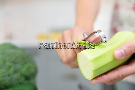 womans hand peeling green fresh zucchini