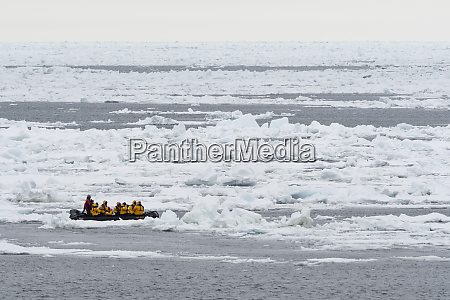 tourists on inflatable boats exploring the