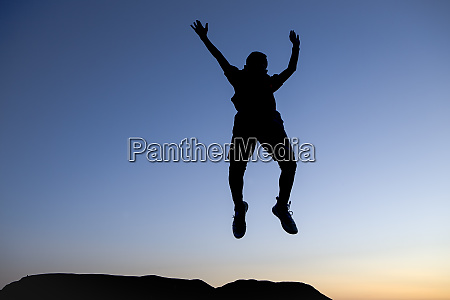 silhouette of boy leaping in the