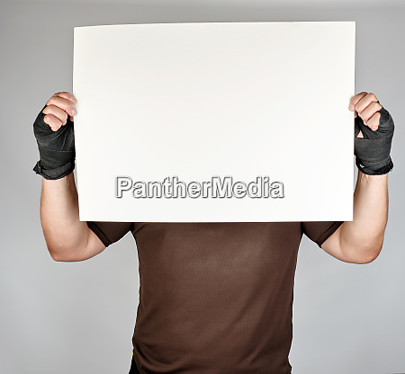 athlete in brown clothes holds a