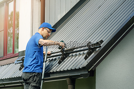roofer installing snow guard on metal