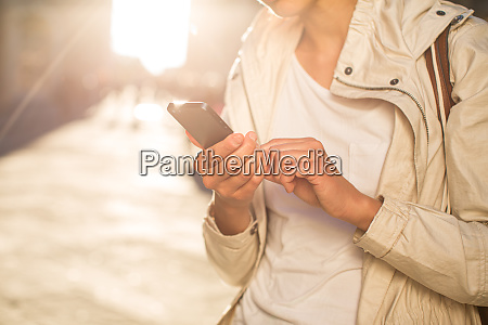 young woman messagingusing app on her