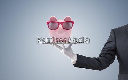 businessman offering piggy bank with pink