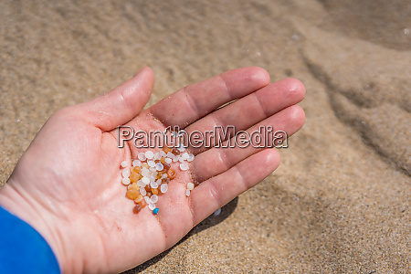woman holding tiny harmful plastic microbeads
