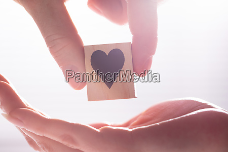 male hand giving wooden block with