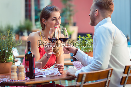 young couple having red wine at