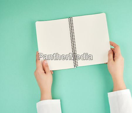 two female hands holding open notepad