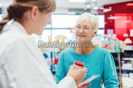 senior woman in pharmacy talking to