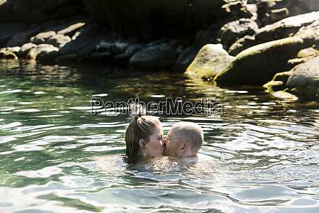 couple kiss while swimming in sea