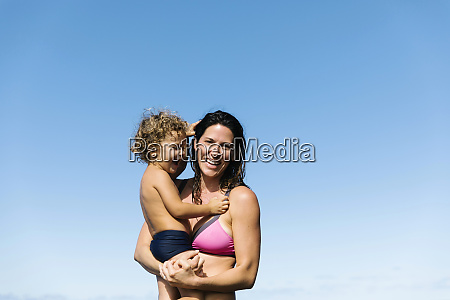 mother carrying her son wearing swimwear