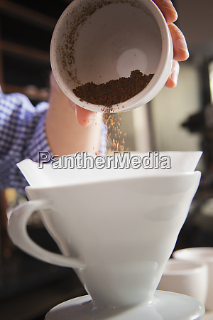 barista pouring coffee grounds into filter