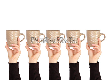 brown ceramic cup in female hand