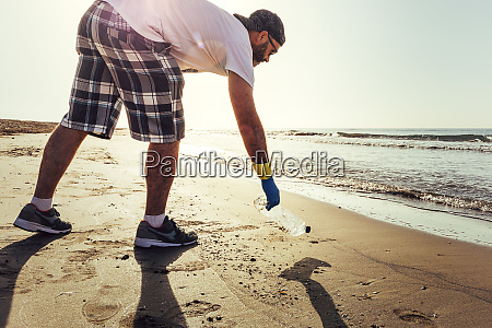 man picking up plastics that pollute
