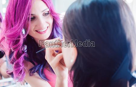 make up artist styling a model