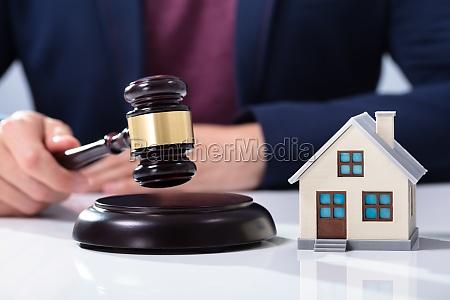 judge striking gavel near house model