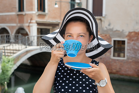 young woman drinking coffee in venice