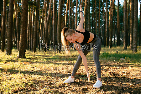 sportive young woman exercising outdoors