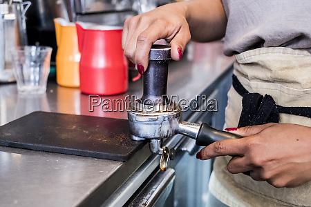 woman barista preparing coffee beans grounds
