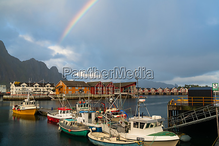 boats in harbour and rainbow at