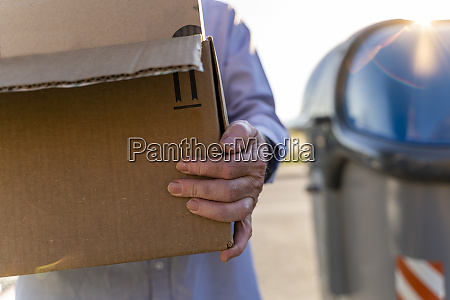 senior man recycling cardboard carrying cardboard