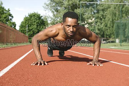athlete doing push ups on racetrack