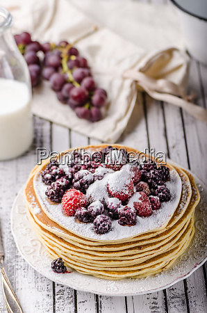 homemade crepes with frozen berries topped