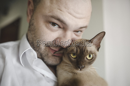 portrait of burmese cat with owner