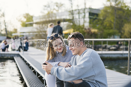young couple sitting on jetty at